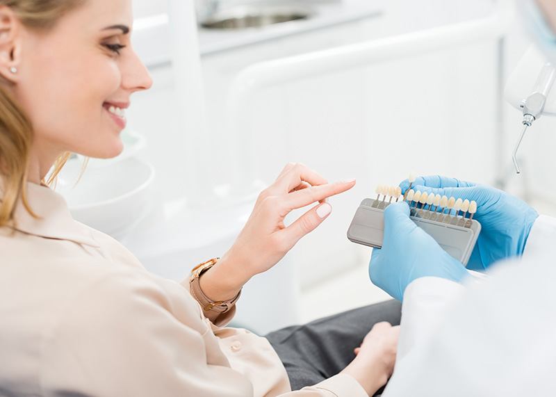 doctor-showing-tooth-implants-to-female-patient-in-9AG2FLZ