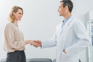 male-doctor-and-female-patient-shaking-hands-in-mo-YRGZXVP