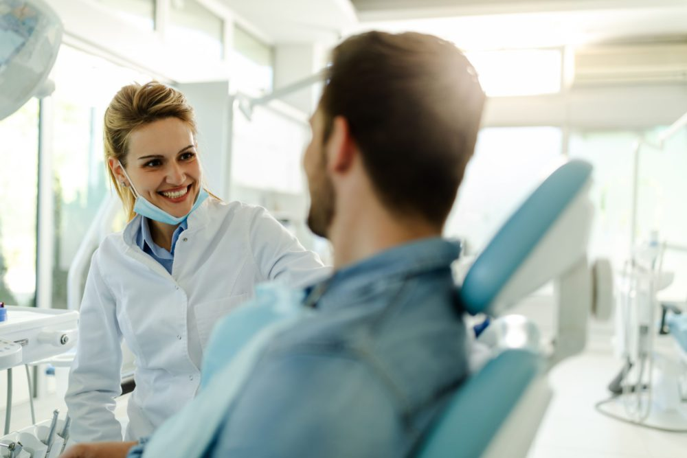 Beautiful female dentist talking with happy male patient at clinic.