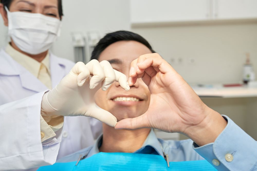 patient-and-dentist-showing-heart-gesture-with-han-2G5ZQAF